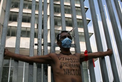 "The writing on his chest says ""VIH-SIDA EMERGENCIA NACIONAL,"" or ""HIV/AIDS National Emergency."""